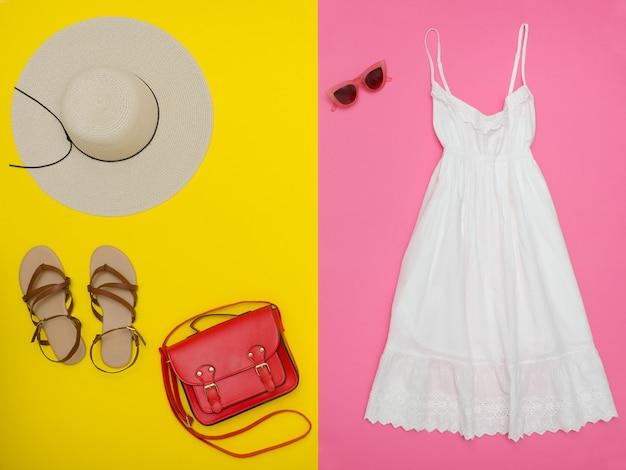 Biała sukienka, czerwona torebka, brązowe buty i okulary przeciwsłoneczne. jasne różowe i żółte tło