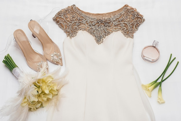 Biała suknia ślubna ozdobiona złotymi koralikami leży obok butów panny młodej ozdobionych kamieniami obok żółtych kwiatów i perfum chanel