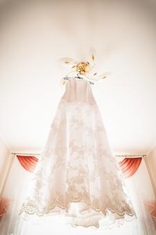 Biała suknia ślubna wisząca na ramionach
