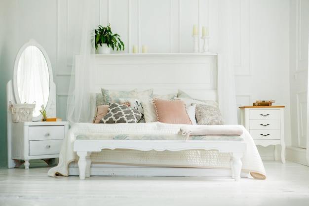 Biała sypialnia w stylu skandynawskim. cztery poduszki są na łóżku. nowoczesne wnętrze