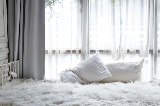 Biała sypialnia z białą zasłoną w oknie