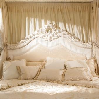 Biała sypialnia z delikatnym światłem na ten romantyczny obraz
