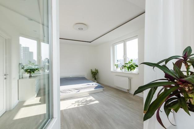 Biała sypialnia z elementami z cegły, balkonem, podwójnym łóżkiem, biurkiem
