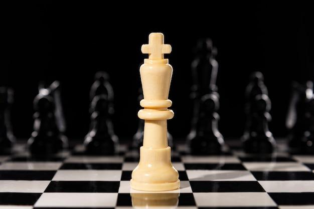 Biała szachowa królowa na szachownicy przeciw czarnym szachowym kawałkom