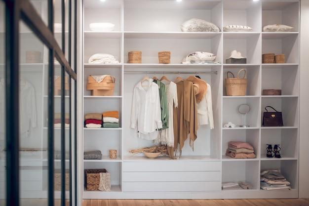 Biała szafa z ubraniami i butami na półkach