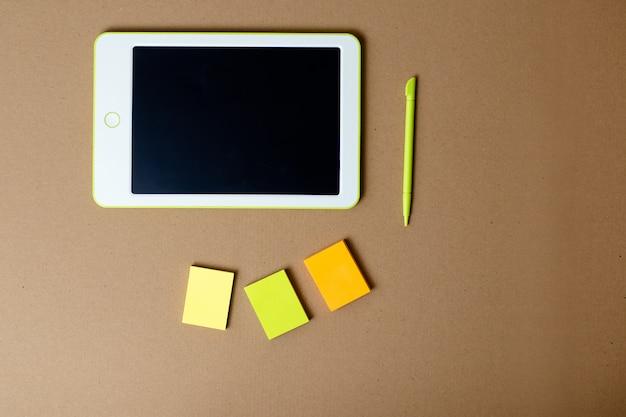 Biała tabletka z piórem i karteczki na tle papieru rzemiosła. domowe biuro podczas samoizolacji, praca w domu. edukacja online, e-learning podczas kwarantanny.