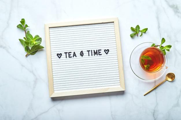 Biała tablica na herbatę z tekstem na marmurowym stole ze szklaną filiżanką herbaty z liśćmi mięty