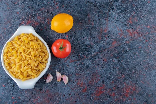 Biała tablica surowego makaronu ze świeżymi czerwonymi pomidorami i cytryną na ciemnym tle.