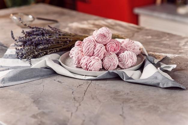 Biała taca ze świeżymi piankami na marmurowym stole z ręcznikiem i lawendą.