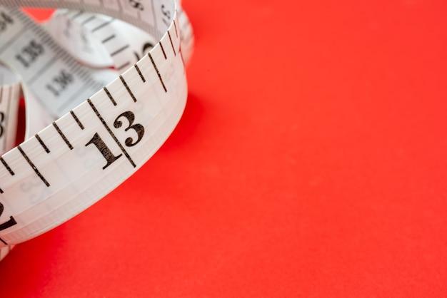 Biała taśma pomiarowa na czerwonym tle. pomiar długości i obwodu. schudnij i przytyj.