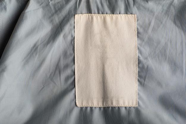 Biała tekstylna metka na szarym materiale. pusta przestrzeń, makieta