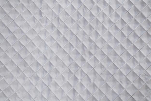 Biała tekstylna tekstura z tłoczonym tłem w kratkę