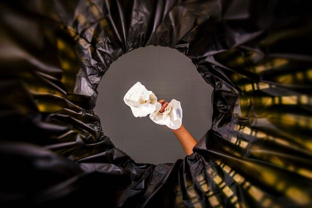 Biała tkanina wrzucona do worka na śmieci