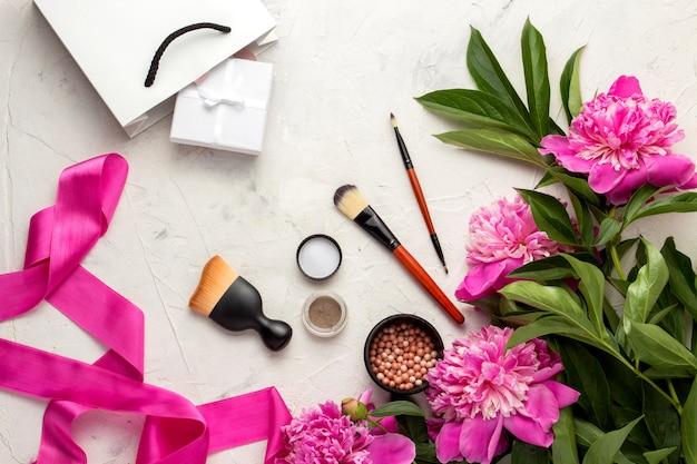 Biała torba prezentowa i zapakowana w prezent, pędzel do różu, cień do powiek oraz różową wstążkę i piwonie. widok z góry.