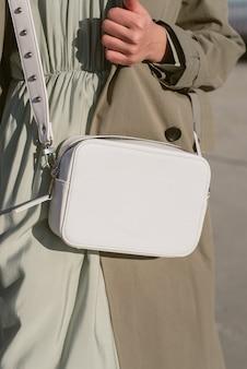 Biała torba w ręku dziewczyny w słońcu