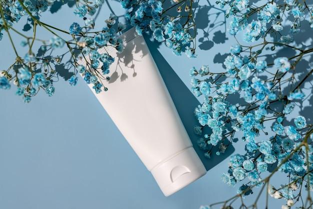 Biała tubka kosmetyczna na niebieskim tle z kwiatami gipsówki. koncepcja kremu z naturalnym składnikiem i nietestowana na zwierzętach.