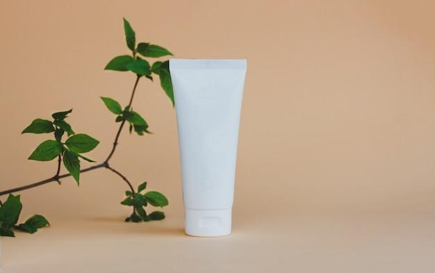 Biała tubka kremowego peelingu lub balsamu stoi na beżowym tle pod zielonymi liśćmi naturalna ekofr...