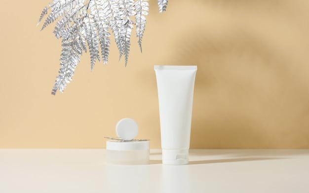 Biała tubka na kosmetyki, słoik kremu i srebrny listek na białym stole. kosmetyk na beżowym tle cienia. butelka z kremem, balsam, środek czyszczący, szampon do pielęgnacji skóry