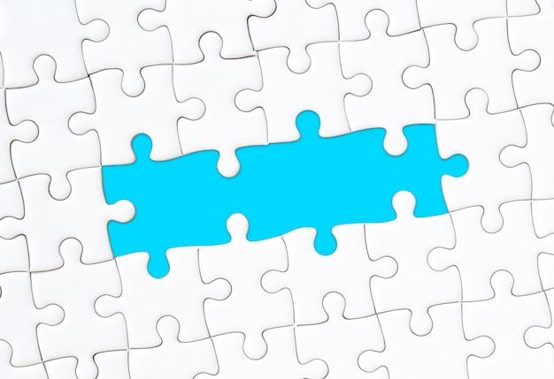 Biała układanka z pustym niebieskim tle