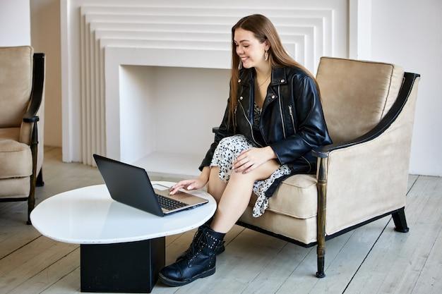 Biała uśmiechnięta kobieta siedzi w biurze z laptopem