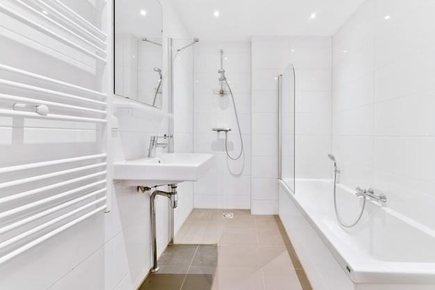 Biała wanna z kranem w nowoczesnej łazience w minimalistycznym stylu w mieszkaniu
