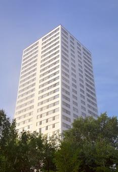 Biała wieża mieszkalnego wieżowca wśród zielonych drzew, błękitne niebo. nowosybirsk, syberia, rosja