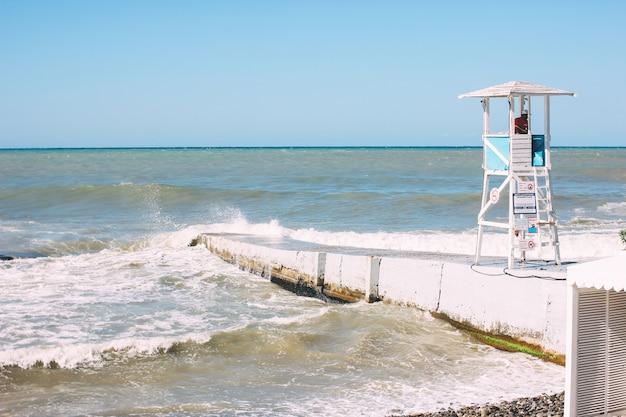Biała wieża z ratownikiem na brzegu szturmującego morza czarnego