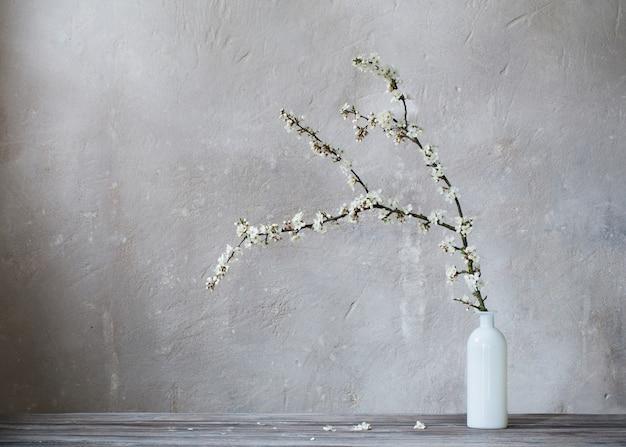 Biała wiśnia kwitnie w wazie na starym szarym tle
