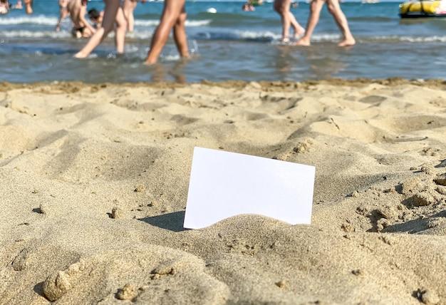 Biała wizytówka leży na piasku