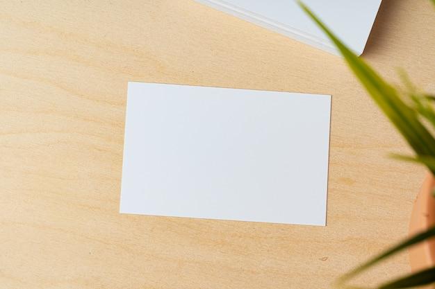 Biała wizytówka na drewnianym stole widok z góry