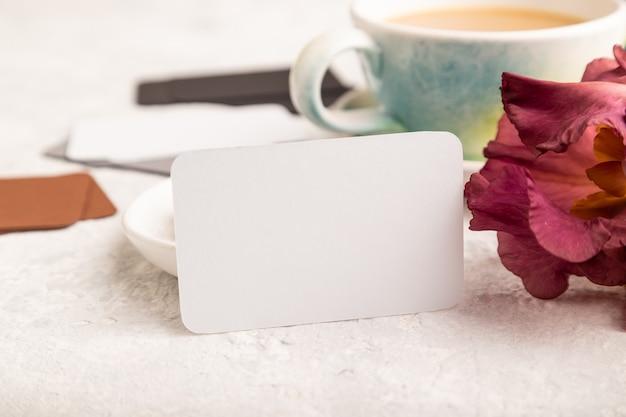 Biała wizytówka z filiżanką cioffee, cukierki czekoladowe i kwiaty tęczówki na szarym tle.