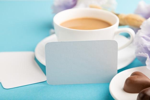 Biała wizytówka z filiżanką cioffee, cukierków czekoladowych i kwiatów tęczówki na niebieskiej powierzchni.