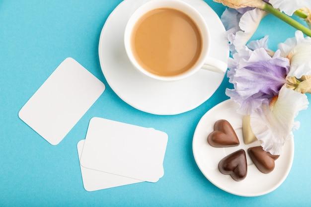 Biała wizytówka z filiżanką cioffee, cukierków czekoladowych i kwiatów tęczówki na niebieskim tle.
