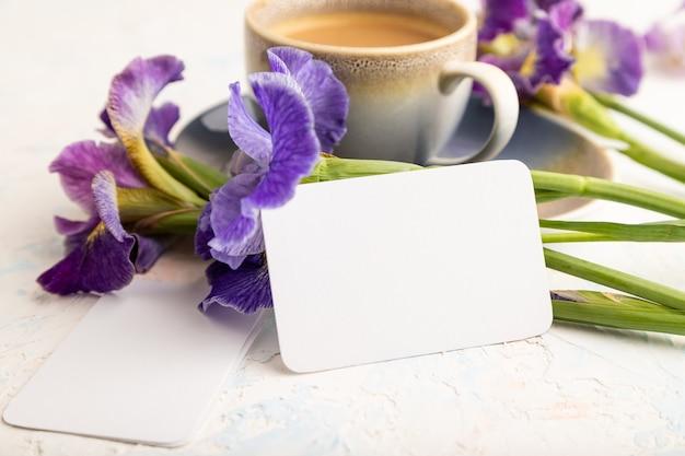 Biała wizytówka z filiżanką cioffee i irysa kwiaty na białym tle betonu. widok z boku,