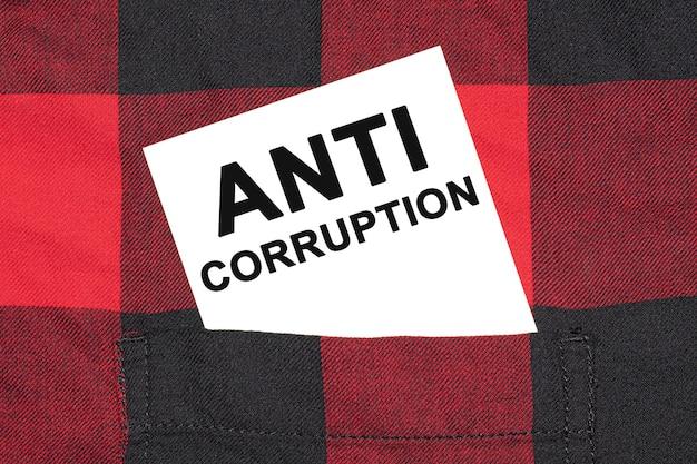 Biała wizytówka z napisem anti corruption leży w rękawie kraciastej koszuli.