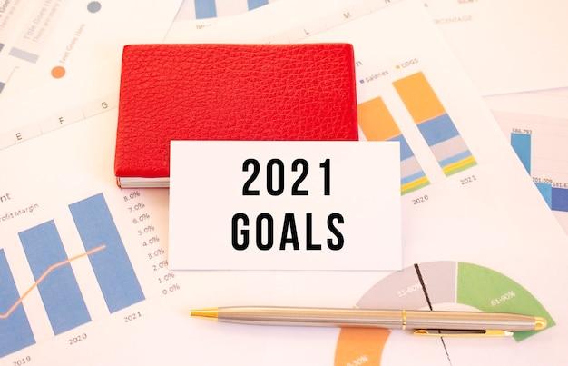 Biała wizytówka z napisem goals 2021 leży obok czerwonego wizytownika. koncepcja finansowa.