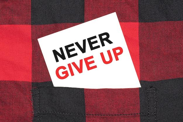 Biała wizytówka z napisem never give up leży w rękawie kraciastej koszuli.