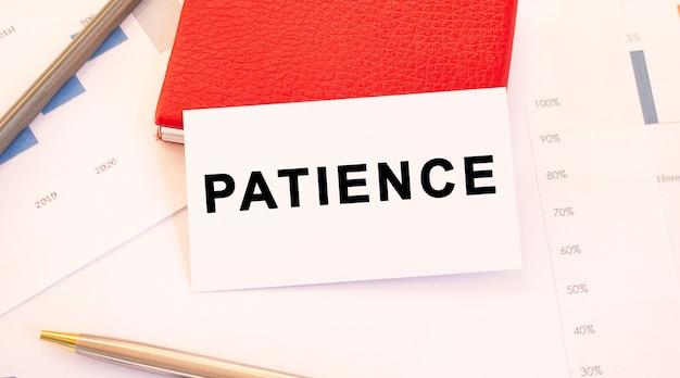 Biała wizytówka z napisem patience leży obok czerwonego wizytownika. koncepcja finansowa.
