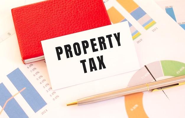 Biała wizytówka z napisem podatek od własności znajduje się obok czerwonego wizytownika
