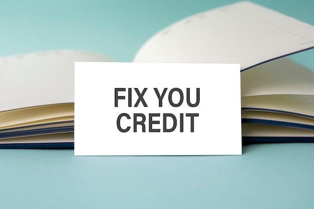 Biała wizytówka z tekstem fix you credit stoi na biurku na tle otwartego pamiętnika. nieostre