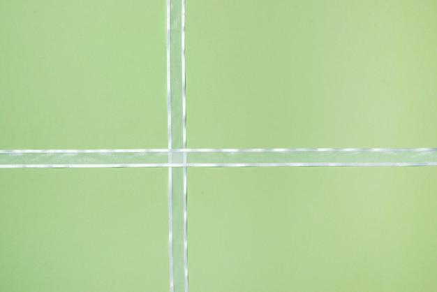 Biała wstążka na zielonym tle.