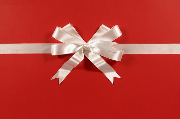 Biała wstążka prezent łuk na czerwonym tle