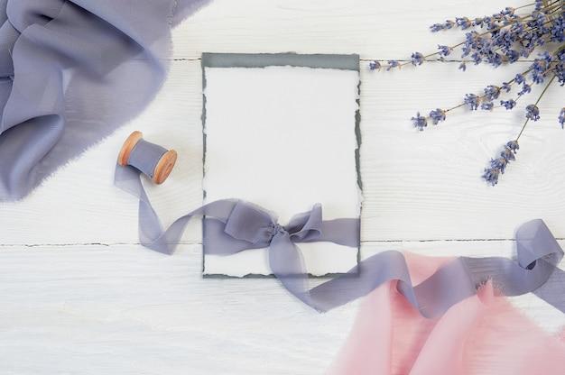 Biała wstążka z pustą kartką z różowo-niebieskim materiałem i lawendowymi kwiatami