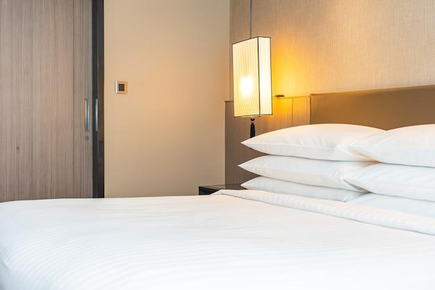 Biała wygodna poduszka i kocyk ozdobiony we wnętrzu sypialni