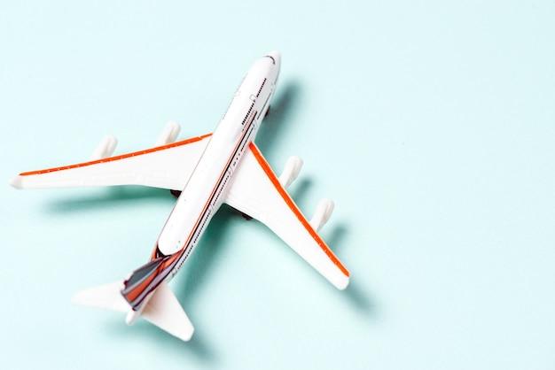 Biała zabawka samolotu na jasnoniebieskim tle. widok z góry
