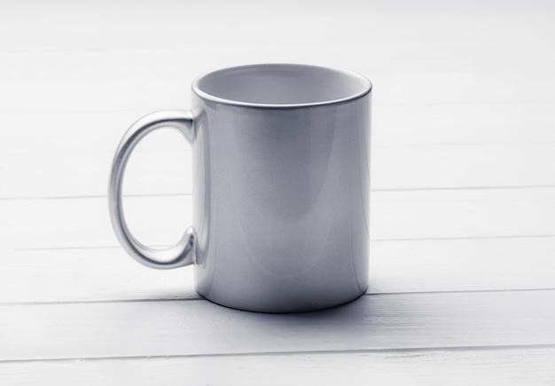 Biała zacieniona filiżanka kawy na białej drewnianej makiecie stołu obiadowego