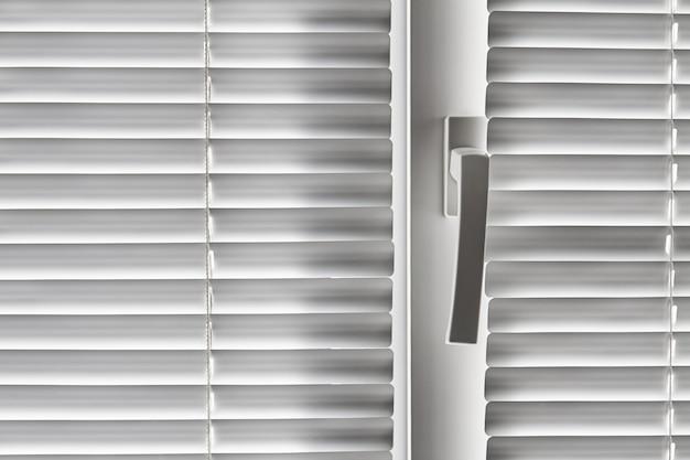 Biała żaluzja na oknie. zbliżenie