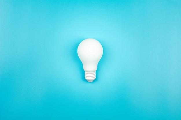 Biała żarówka świeci na niebieskim stole. rozwój działalności gospodarczej