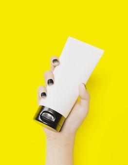 Biała żeńska ręka trzyma słoik kremu kosmetycznego na żółtej powierzchni
