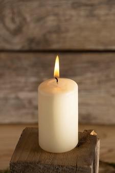 Biała zimowa świeca na drewnianym sześcianie